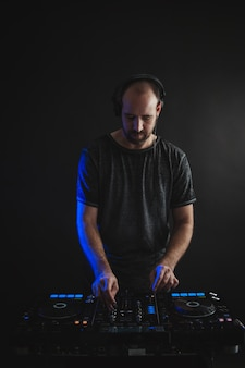 Vertical picture of a male dj working under the lights against a dark background in a studio