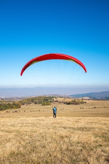 Vertical picture of a man flying with a red parachute surrounded by greenery under a blue sky