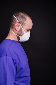 Vertical picture of a man with a face mask against a dark background - covid-19