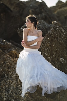 Вертикальный снимок брюнетки в белом платье, позирующей на скалах