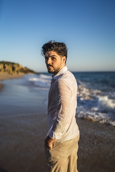 Вертикальное изображение мужчины брюнетки на волнистом океане