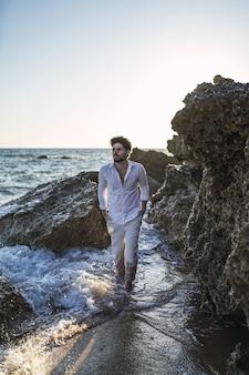 崖の横の水の上を歩いているブルネットの男性の垂直方向の写真