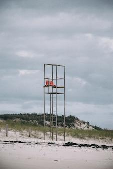 昼間の曇り空の下のビーチにあるライフガードタワーの垂直方向の写真