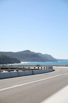 산과 바다에 대항하는 긴 구불 구불 한 도로의 세로 그림