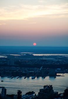Вертикальный снимок города в окружении моря под солнечным светом во время заката вечером