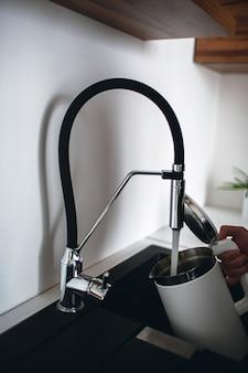 남자의 손이 위쪽이 열린 전기 주전자를 들고 수도꼭지에서 물을 붓는 수직 그림. 물을 데울 필요가 있습니다. 좋은 장비와 배관을 갖춘 현대적인 주방