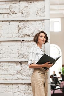 Вертикальная картина задумчивой кудрявой женщины-менеджера
