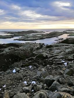 ノルウェーのラッケで日没時に海に囲まれた岩の垂直方向の画像