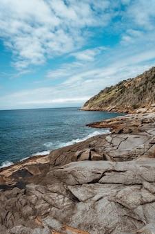 リオデジャネイロの青い空と日光の下で海に囲まれた岩の垂直方向の写真