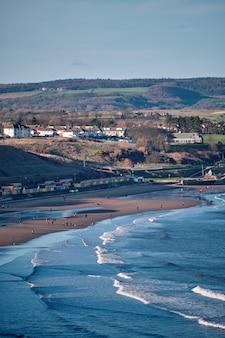 英国の緑に覆われた丘に囲まれたスカーバラ海岸の垂直方向の画像