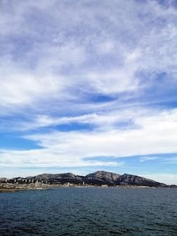フランスのマルセイユで曇り空の下の岩に囲まれた海の垂直方向の画像
