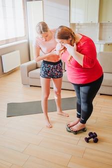 太りすぎの女の子が体重計に立つのを助ける若いスリムモデルの垂直方向の画像。
