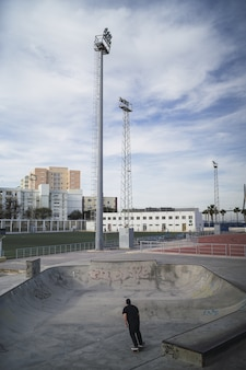 Vertical picture of a person skateboarding in a skate park under a cloudy sky at daytime