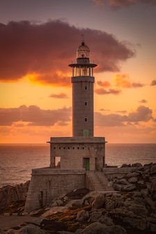 Vertical picture of the punta nariga lighthouse surrounded by the sea during the sunset in spain
