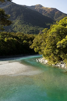 Vertical picture of a river surrounded by hills covered in forests under the sunlight