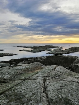 Vertical picture of rocks surrounded by the sea during the sunset in rakke in norway