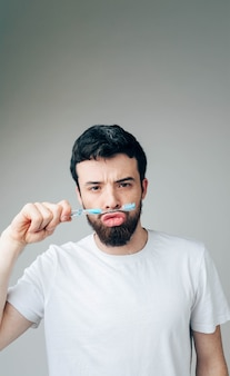 Vertical picture of serious funny peaceful guy playing with toothbrush. hold it between mouth and nose. healthcare concept