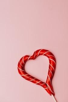 ハートの形で甘い赤いキャラメルと垂直ピンクの背景。バレンタインデーのギフト。無料の場所。