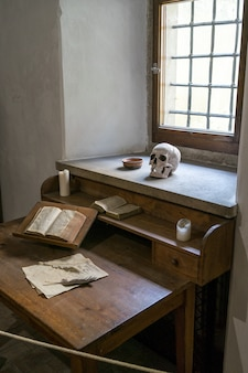 Vertical of a poet's room with a skull, papers and a book on the work desk