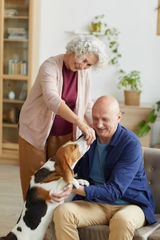 Vertical portrait of adorable senior couple playing with dog asking for treats in cozy home interior