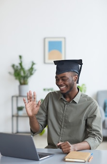 Vertical portrait of african-american young man wearing graduation cap and waving at camera while sharing news with friends and family by video chat, copy space