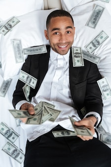 Vertical portrait of african man in suit lying on bed in hotel room and throws the money. top view