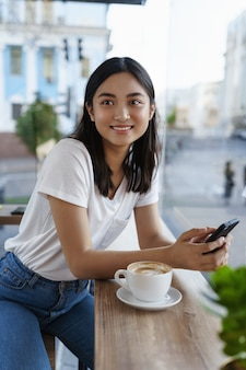 Vertical portrait of asian woman sitting in city cafe near window at summer day, holdingmobile phone and drinking coffee, smiling aside