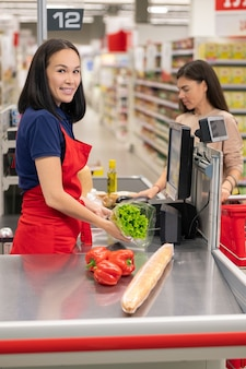 Vertical portrait of attractive asian cashier wearing red apron working at cash desk beeping goods for customer