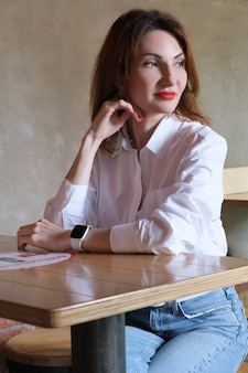 Vertical portrait of an attractive young woman with red hair in jeans and a white shirt at a wooden table in a cafe. the woman rests her head with her hand and looks thoughtfully to the side.