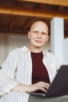 Vertical portrait of bald adult woman smiling at camera while holding laptop and working at home in modern interior, alopecia and cancer awareness
