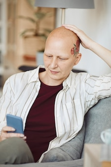 Vertical portrait of bald adult woman with head tattoo using smartphone while sitting in cozy armchair at home, alopecia and cancer awareness