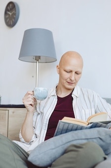 Vertical portrait of bald mature woman reading book sitting in comfortable armchair at home and enjoying cup of coffee, alopecia and cancer awareness, copy space