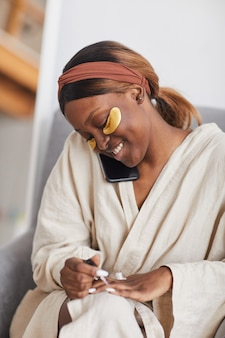 Vertical portrait of beautiful african-american woman enjoying skincare routine at home and doing manicure while speaking by phone