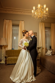 Vertical portrait of beauty jusm married couple at home hugging