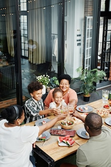 Vertical portrait of big africanamerican family clinking glasses while enjoying dinner together outd...