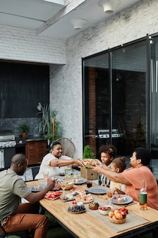 Vertical portrait of big africanamerican family sitting at table and enjoying dinner together outdoo...