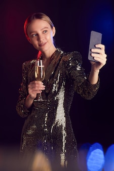 Vertical portrait of blonde young woman livestreaming or taking selfie photo while enjoying party in night club