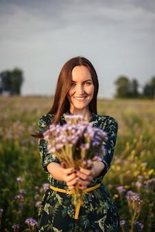 Vertical portrait of a brunette girl in a flower field gives a bouquet of fresh purple wild flowers