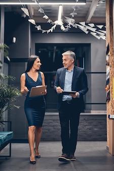 Вертикальный портрет деловых людей, идущих в современном офисе во время разговора