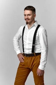 Ritratto verticale di affascinante modello maschio europeo giovane carismatico con taglio di capelli alla moda