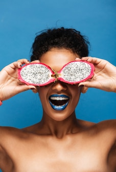 Vertical portrait of cheerful african american woman fooling around while covering eyes with exotic pitahaya fruit cut in half isolated,  over blue