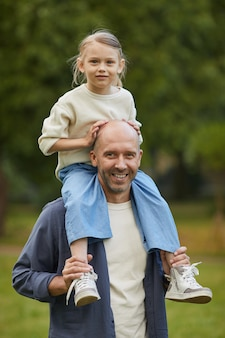 Vertical portrait of cute girl sitting on dads shoulders and enjoying walk in park