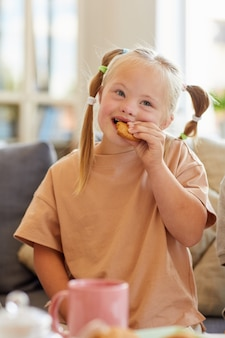 Vertical portrait of cute girl with down syndrome eating cookie while enjoying tea with family at home