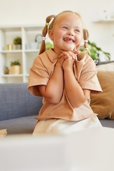 Vertical portrait of cute girl with down syndrome laughing happily while sitting on couch in sunlit room