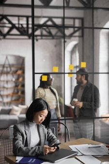 Vertical portrait of elegant asian businesswoman working at table in graphic grey office interior, copy space