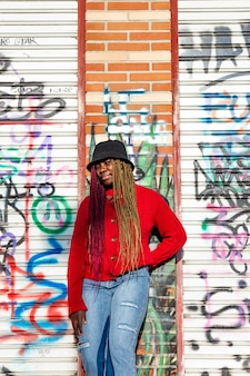 Vertical portrait of an exotic black girl with colored braids. dressed with a red sweater and a black hat. graffiti wall background