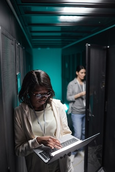 Vertical portrait of female data engineer using laptop in server room while setting up supercomputer network, copy space