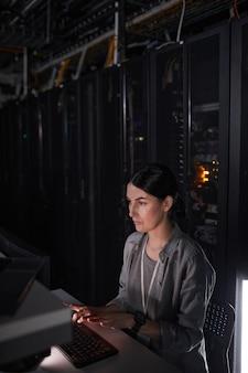 Vertical portrait of female network engineer using computer while working in dark server room, copy space