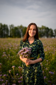 Vertical portrait of a girl with a bouquet of wild flowers in the field at sunset