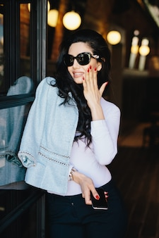 Vertical portrait of glamour businesswoman with dark luxurious hair wearing sunglasses and formal clothes
